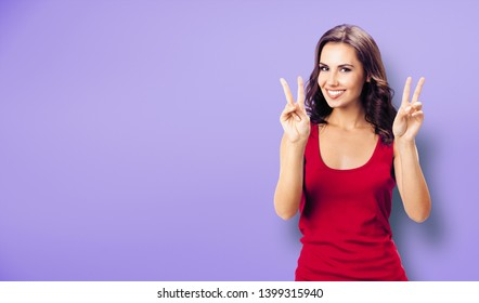 Portrait photo - young happy smiling woman in casual clothing, showing two fingers or victory gesture, over violet color background. Happy girl in red dress. Brunette excited model at studio picture.