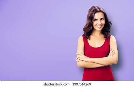 Portrait photo - young smiling woman in casual red clothing, in crossed arms pose. Violet color wall background. Happy beautiful girl at studio. Brunette Model with long hair posing at studio picture.