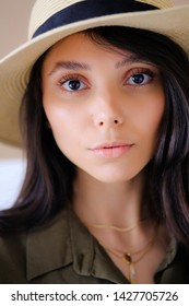 Portrait of a photogenic portfolio of a young model of a girl in a straw hat looking at the camera with a calm look. The concept of fashion and style, cosmetology, natural female beauty.