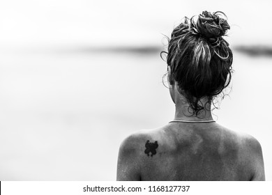 A portrait photograph of a cute girl with a tattoo on the scapula looking to the horizon at a wild beach in Uruguay, South America