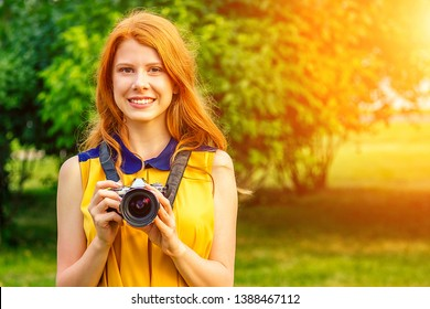 portrait of photosession professional beautiful young ginger redhead irish girl in a yellow dress photographed in the summer park. photographer in photoshoot with a big camera and a cool lens