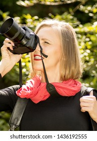 Portrait of photosession professional blonde woman in the summer park. Photographer in photoshoot with a big camera and a cool lens