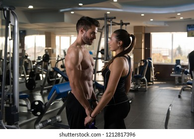 Portrait Of A Physically Fit Couple Showing Their Well Trained Body with Kettle Bell - Muscular Athletic Bodybuilder Fitness Model Posing After Exercises