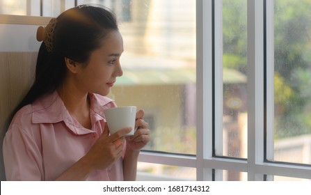 The portrait picture of Asian female working at home, looking outside the window and drinking a cup of coffee, close up view, startup small business owner idea, businesswoman successful concept