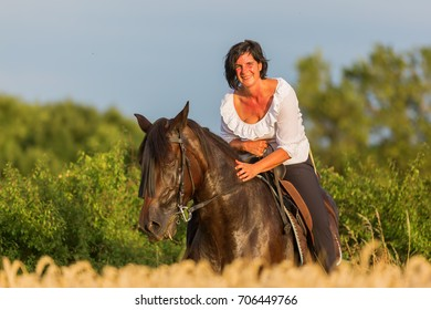 portrait picture of a mature woman on an Andalusian horse