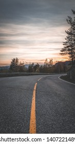 Portrait Picture, road in mountains, Norway. Beautiful sunset or sunrise in Viking land. Yellow road markings, family trip in summer, beautiful Norway. Mountains rivers and lakes