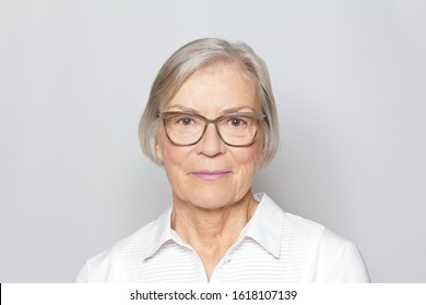 Portrait picture of a senior woman wearing glasses on neutral gray background.