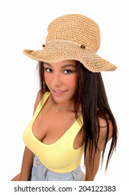 A portrait picture of a teenager girl wearing a yellow t-shirt an a straw hat, standing isolated for white background.