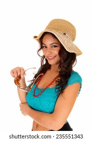 A portrait picture of a teenager girl wearing a turquoise blouse, a straw hat and sunglasses, standing isolated for white background.