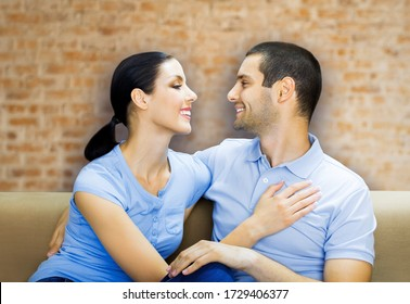 Portrait picture of young happy smiling attractive amorous embracing couple, looking at each other, over loft style wall, indoors.