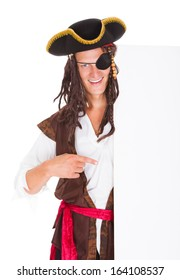 Portrait Of A Pirate Pointing At Blank Placard Over White Background
