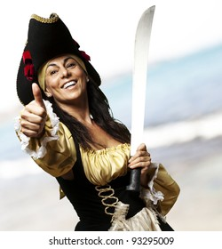 portrait of a pirate woman holding a sword and gesturing ok at the beach