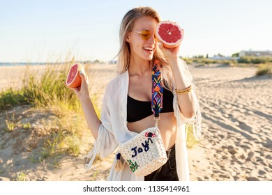 Portrait of playful carefree woman posing with tasty grapefruit halves in hands. Wearing stylish glasses and boho beach outfit. Warm sunset colors. Shining  blonde hairs.