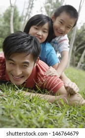 Portrait of playful father with children lying on grass at park