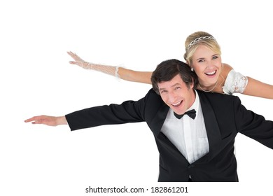 Portrait of playful groom with arms outstretched carrying bride on back over white background