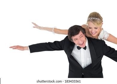 Portrait of playful newly wed couple with arms outstretched over white background