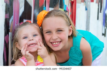 Portrait of playful sisters smiling very happy.