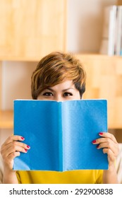 Portrait of playful woman hiding behind a book
