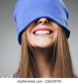 Portrait of playful woman in knitted winter cap smiling