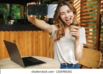 Portrait of a playful young girl taking selfie with mobile phone while sitting with laptop computer and holding coffee cup at a cafe outdoors