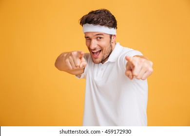 Portrait of playful young man athlete winking and pointing on you over yellow background