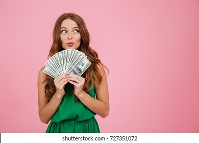 Portrait of a playful young woman with long hair holding bunch of money banknotes and looking away at copy space isolated over pink background