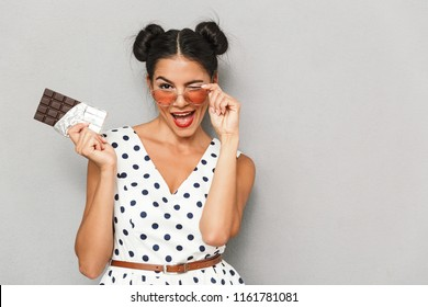 Portrait of a playful young woman in summer dress and sunglasses isolated, holding chocolate bar