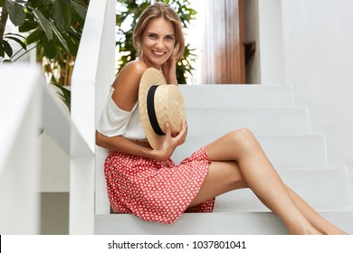 Portrait of pleasant looking female wears fashionable blouse and polka dot skirt, holds straw hat, has slender legs, smiles joyfully at camera, rejoices good rest in tropics. Beauty and rest concept