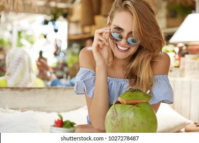 Portrait of pleasant looking happy female model wears stylish blouse and sunglasses, being on resort, enjoys coconut cocktail, looks with pleased expression into camera. Fashionable tourist in cafe
