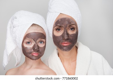 Portrait of pleasant middle-aged mother in bathrobe and her little daughter are standing together with towels on head and facial clay mask while enjoying spa procedures. Isolated. Beauty concept