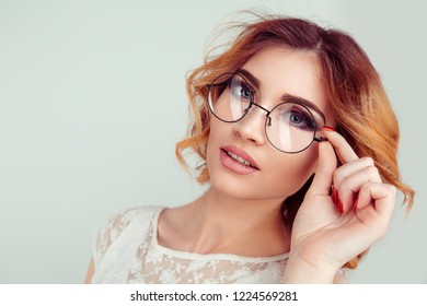 Portrait of pleased attractive smiling female dressed in fashionable lace dress posing, isolated over light green studio background. Stylish curly blonde young European woman holding round glasses.