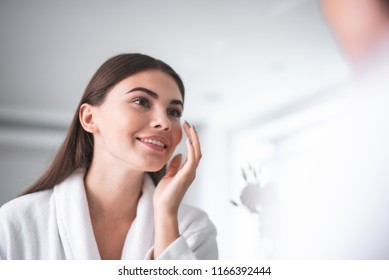 Portrait of pleased girl putting cosmetic ointment on face while watching at mirror indoor. Glad female during skin care concept