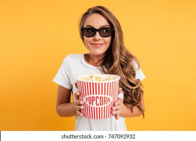 Portrait of a pleased happy girl in 3d glasses holding bucket of popcorn and looking away isolated over yellow background
