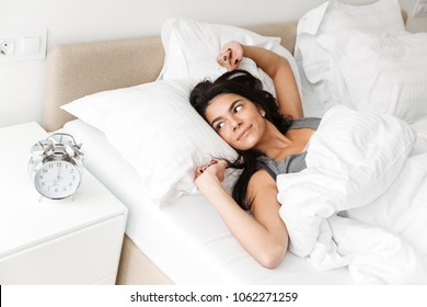 Portrait of pleased relaxed woman stretching in bed at bedroom with white clean linen and looking on alarm clock on nightstand