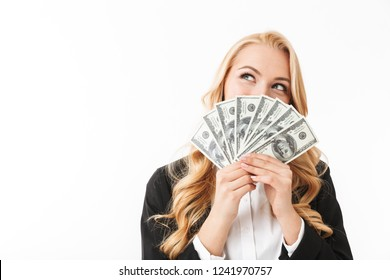Portrait of pleased woman wearing office clothing holding fan of money isolated over white background