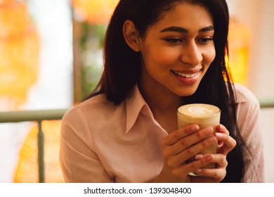 Portrait of a pleased young dark haired woman feeling good and smiling while having a glass of latte in her hands