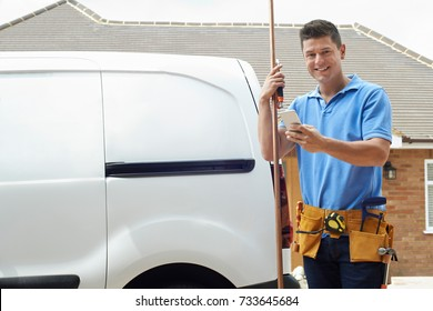 Portrait Of Plumber With Van Texting On Mobile Phone Outside House