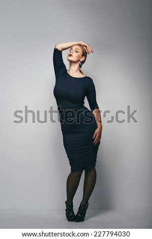 77871b50148 Portrait of a plus size female model posing in black dress over grey  background. Beautiful