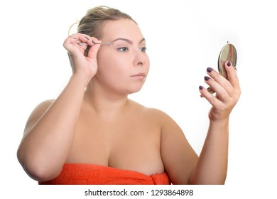Portrait of a plus size woman tweezing eyebrows isolated on white background. The modern concept of eyebrow correction, beauty, fashion, skin care.