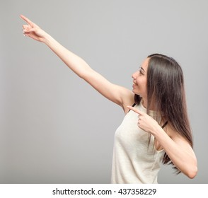 Portrait of pointing beautiful casual girl isolated on gray background