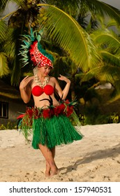 Portrait of Polynesian Pacific Island Tahitian female  dancer  in colorful costumedancing on tropical beach with palm trees in the background.