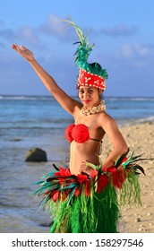 Portrait of Polynesian Pacific Island Tahitian female dancer in colorful costume dancing on tropical beach.