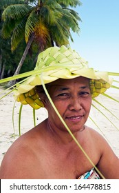 Portrait of Polynesian Pacific Island Tahitian mature female wearing here handcraft of a hat knees out of palm leaveson tropical beach in Aitutaki lagoon Cook Islands.