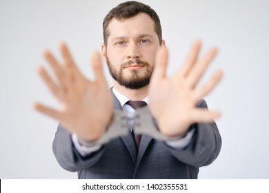 Portrait of poor company businessman showing handcuffed arms. Upset bearded model with stylish hairstyle posing in studio. Scared guy looking at camera with melancholy. Bribe concept isolated on grey