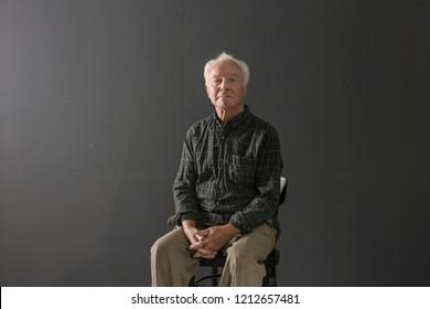 Portrait of poor elderly man sitting on chair against dark background