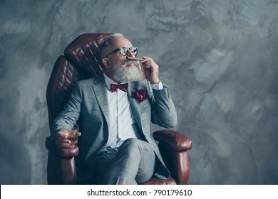 Portrait of posh classy chic elegant rich stunning luxurious millionaire sharp-dressed with maroon pocket tissue relaxing on leather armchair holding cigarette and whisky isolated on grey background