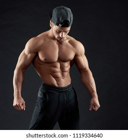 Portrait of posing bodybuilder wearing a cap. Demonstrating his muscles relief and strong arms, clear muscular ABS. Training everyday, working hard. Sport lifestyle. Standing on black background.