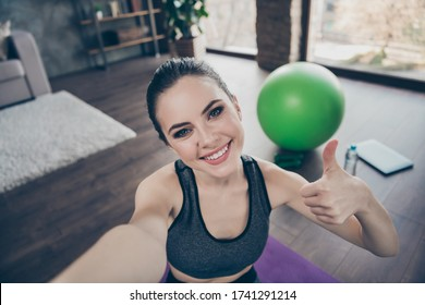 Portrait of positive active energy beautiful girl make selfie show thumb up sign enjoy practice aerobics yoga intense endurance effort regime exercise wear sport outfit in house indoors