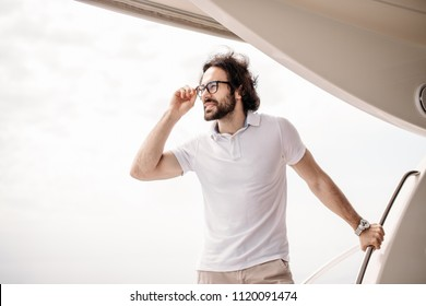 Portrait of positive adult caucasian bearded tourist taking not far-avay sea journey on luxury white yacht in Caribbean sea