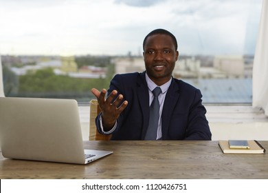 Portrait of positive Afro American male human resource manager in elegant suit sitting in his modern office in front of open laptop computer, reaching out hand to camera, greeting you at large company